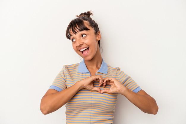 Jeune femme métisse isolée sur fond blanc souriant et montrant une forme de coeur avec les mains.