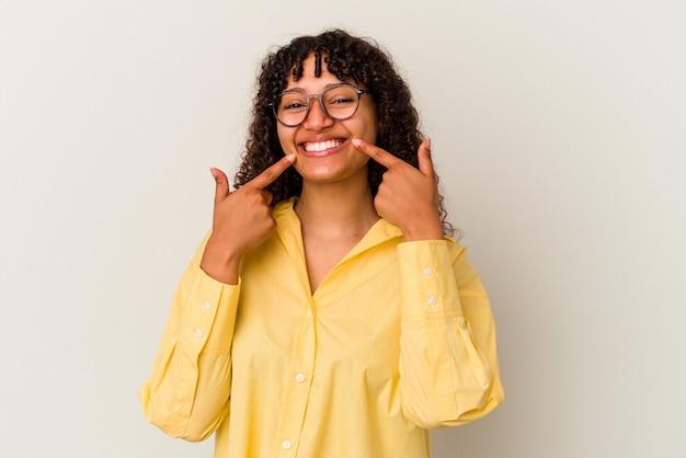 Jeune femme métisse isolée sur fond blanc sourit, pointant du doigt la bouche.