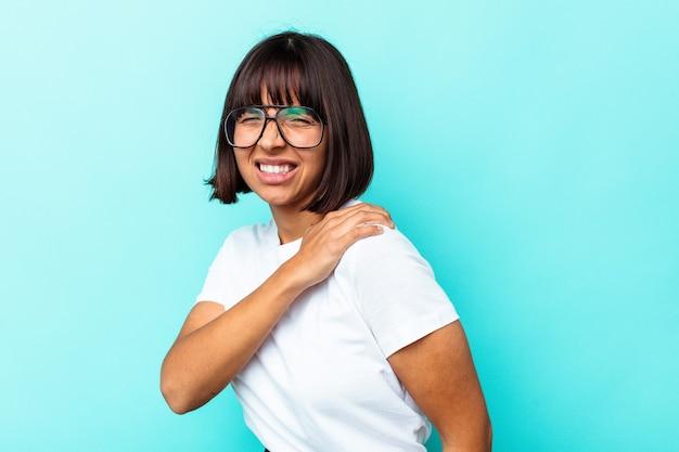 Jeune femme métisse isolée sur fond bleu ayant une douleur à l'épaule.