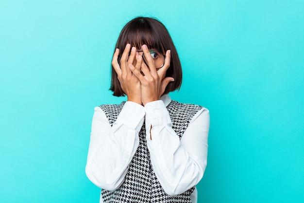 Jeune femme métisse isolée sur fond bleu clignote à travers les doigts effrayés et nerveux.