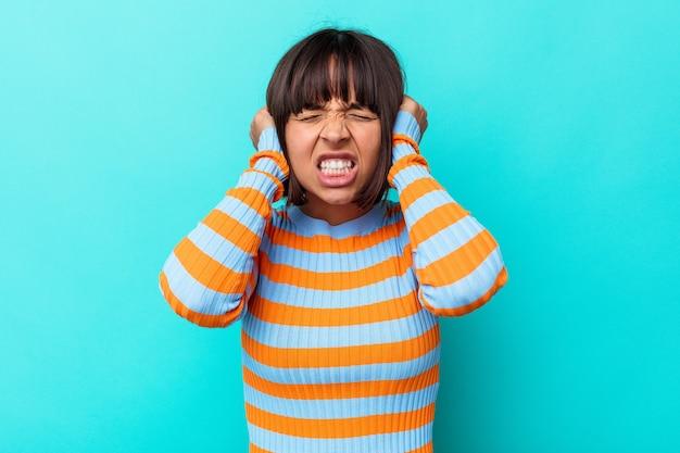 Jeune femme métisse isolée sur fond bleu couvrant les oreilles avec les mains.