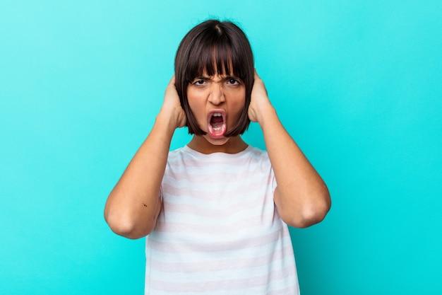 Jeune femme métisse isolée sur fond bleu criant de rage.