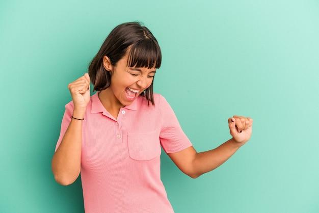 Jeune femme métisse isolée sur fond bleu dansant et s'amusant.