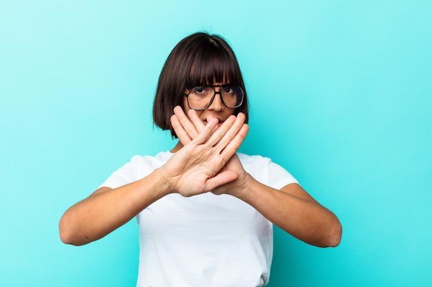 Jeune femme métisse isolée sur fond bleu faisant un geste de déni
