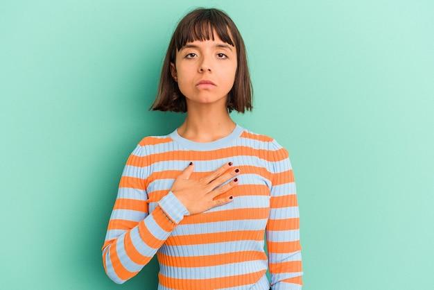 Jeune femme métisse isolée sur fond bleu prêtant serment, mettant la main sur la poitrine.