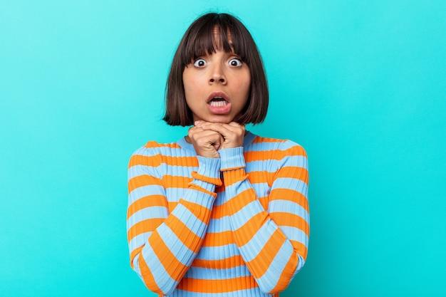 Jeune femme métisse isolée sur fond bleu priant pour la chance, étonnée et ouvrant la bouche regardant vers l'avant.