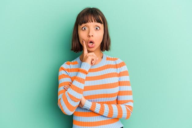 Jeune femme métisse isolée sur fond bleu se sent confiante en donnant un câlin à la caméra.