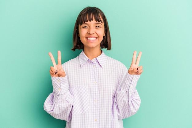 Jeune femme métisse isolée sur fond bleu sourit, pointant du doigt la bouche.