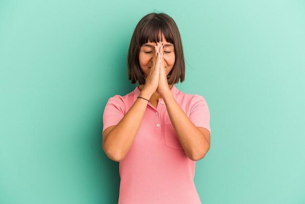 Jeune femme métisse isolée sur fond bleu tenant la main en prière près de la bouche, se sent confiante.
