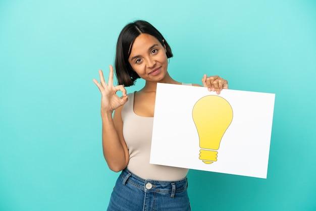 Jeune femme métisse isolée sur fond bleu tenant une pancarte avec icône ampoule avec signe ok