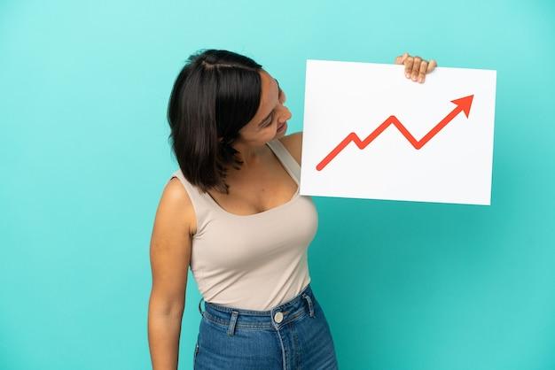 Jeune femme métisse isolée sur fond bleu tenant une pancarte avec un symbole de flèche de statistiques croissante avec une expression heureuse