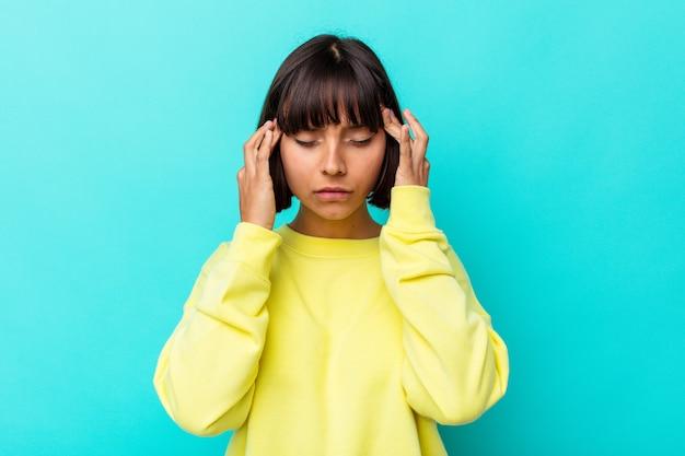 Jeune femme métisse isolée sur fond bleu touchant les tempes et ayant des maux de tête.