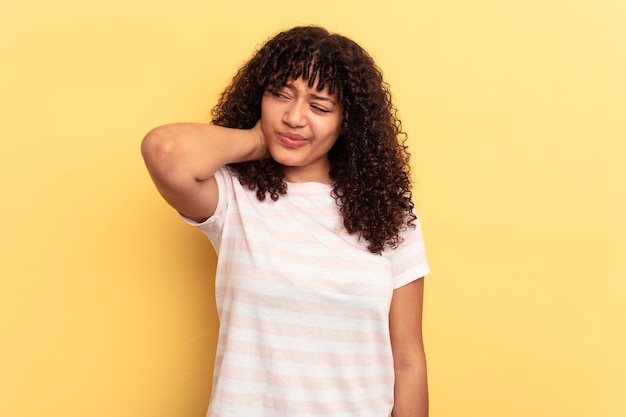 Jeune femme métisse isolée sur fond jaune ayant une douleur au cou due au stress, en la massant et en la touchant avec la main.
