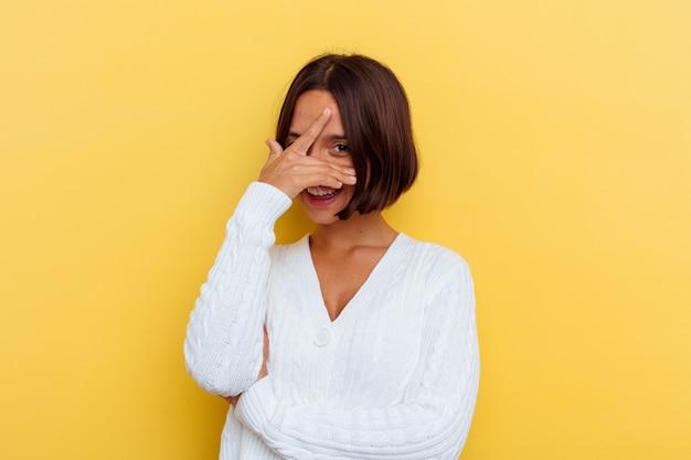 Jeune femme métisse isolée sur fond jaune clignote à la caméra à travers les doigts, visage gêné couvrant.
