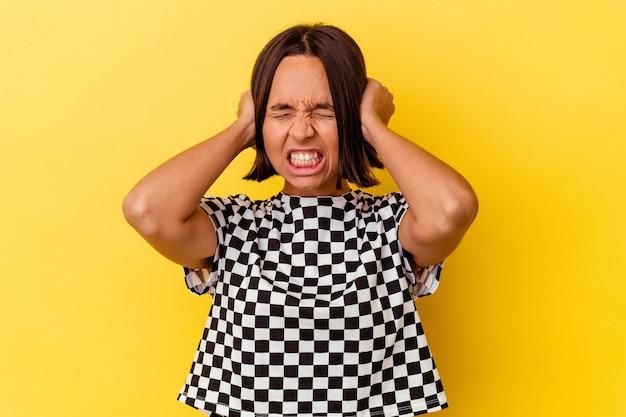 Jeune femme métisse isolée sur fond jaune couvrant les oreilles avec les mains.