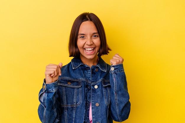 Jeune femme métisse isolée sur fond jaune dansant et s'amusant.