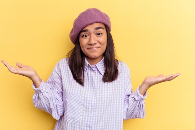 Jeune femme métisse isolée sur fond jaune doutant et haussant les épaules dans un geste de questionnement.