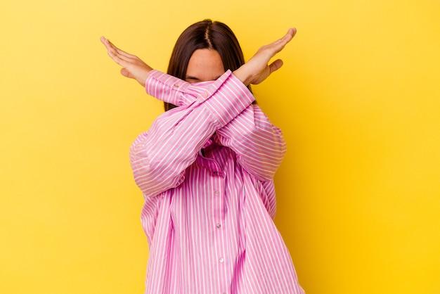 Jeune femme métisse isolée sur fond jaune en gardant les deux bras croisés, concept de déni.