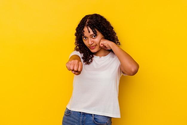 Jeune femme métisse isolée sur fond jaune jetant un coup de poing, colère, combat à cause d'une dispute, boxe.