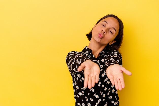 Jeune femme métisse isolée sur fond jaune pliant les lèvres et tenant les paumes pour envoyer un baiser aérien.