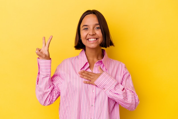 Jeune femme métisse isolée sur fond jaune prêtant serment, mettant la main sur la poitrine.