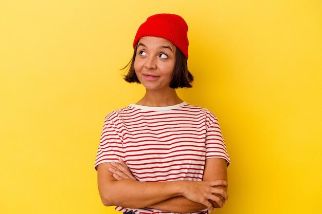 Jeune femme métisse isolée sur fond jaune rêvant d'atteindre des objectifs et des buts