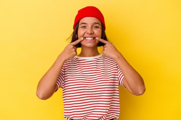 Jeune femme métisse isolée sur fond jaune sourit, pointant du doigt la bouche.