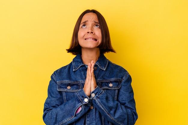 Jeune femme métisse isolée sur fond jaune tenant la main en prière près de la bouche, se sent confiante.