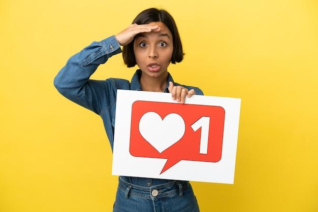 Jeune femme métisse isolée sur fond jaune tenant une pancarte avec comme icône avec expression surprise