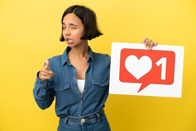 Jeune femme métisse isolée sur fond jaune tenant une pancarte avec comme icône et pointant vers l'avant