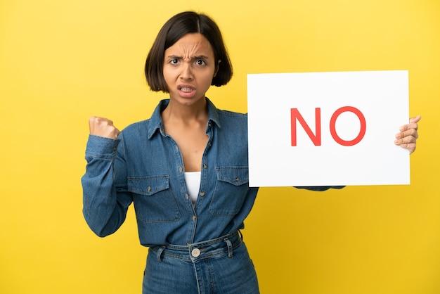 Jeune femme métisse isolée sur fond jaune tenant une pancarte avec texte non et en colère