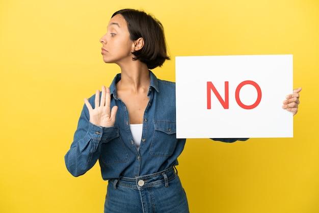 Jeune femme métisse isolée sur fond jaune tenant une pancarte avec le texte non et faisant un panneau d'arrêt