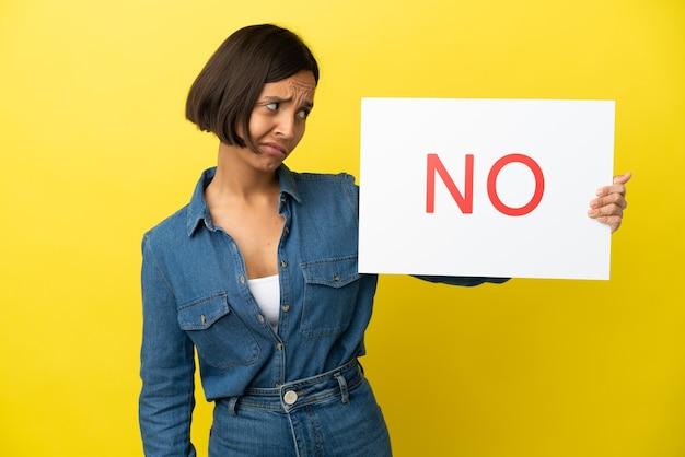 Jeune femme métisse isolée sur fond jaune tenant une pancarte avec texte non