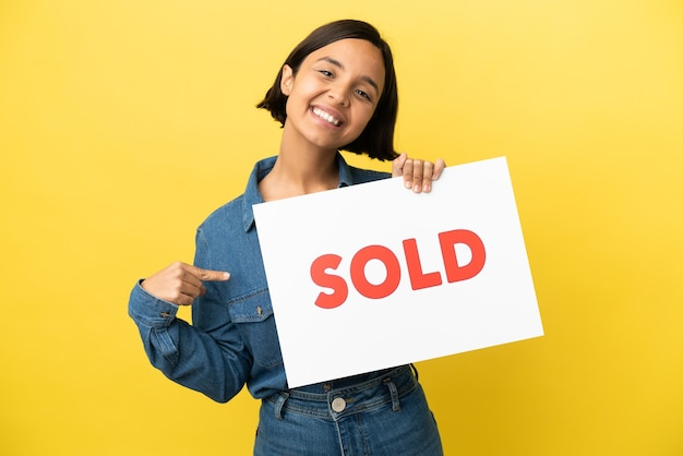 Jeune femme métisse isolée sur fond jaune tenant une pancarte avec texte vendu et en le pointant