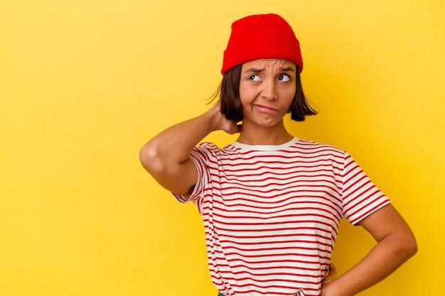 Jeune femme métisse isolée sur fond jaune touchant l'arrière de la tête, pensant et faisant un choix.
