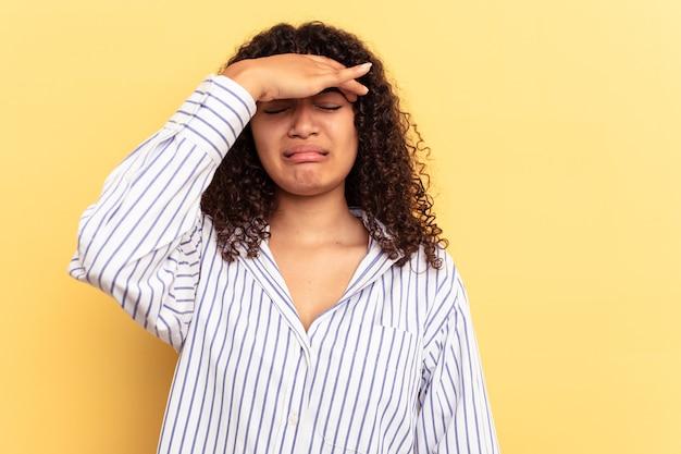 Jeune femme métisse isolée sur fond jaune touchant les tempes et ayant des maux de tête.