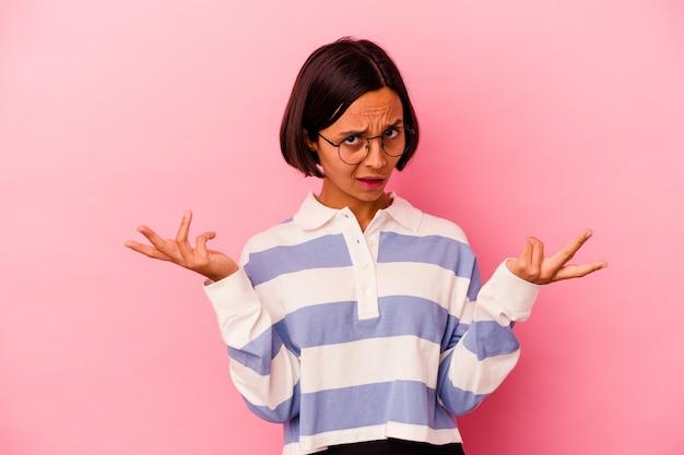 Jeune femme métisse isolée sur fond rose doutant et haussant les épaules dans un geste de questionnement.