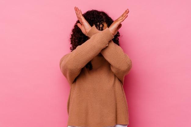Jeune femme métisse isolée sur fond rose en gardant les deux bras croisés, concept de déni.