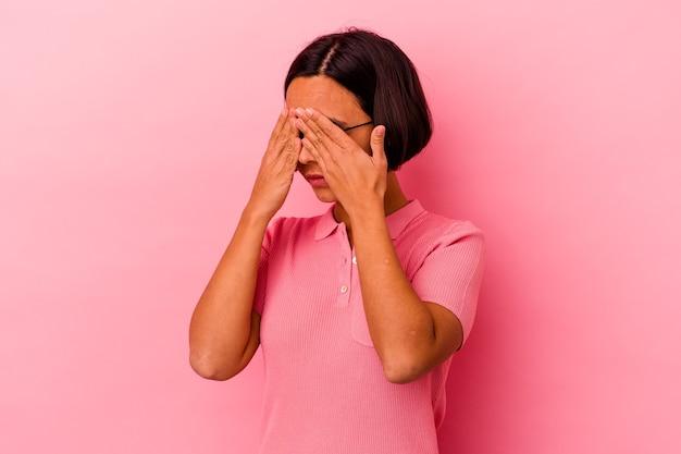 Jeune femme métisse isolée sur fond rose peur couvrant les yeux avec les mains.