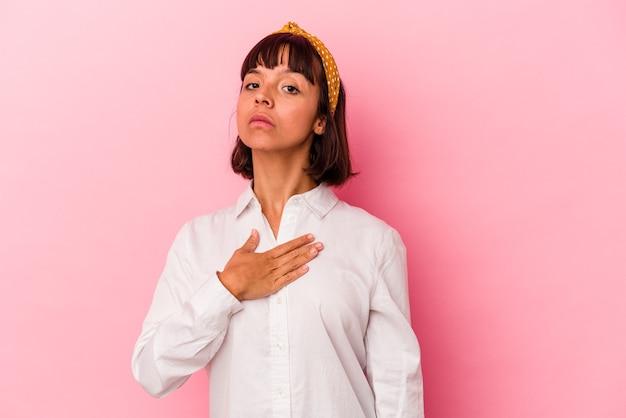 Jeune femme métisse isolée sur fond rose prêtant serment, mettant la main sur la poitrine.