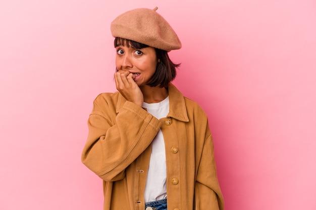 Jeune femme métisse isolée sur fond rose se rongeant les ongles, nerveuse et très anxieuse.