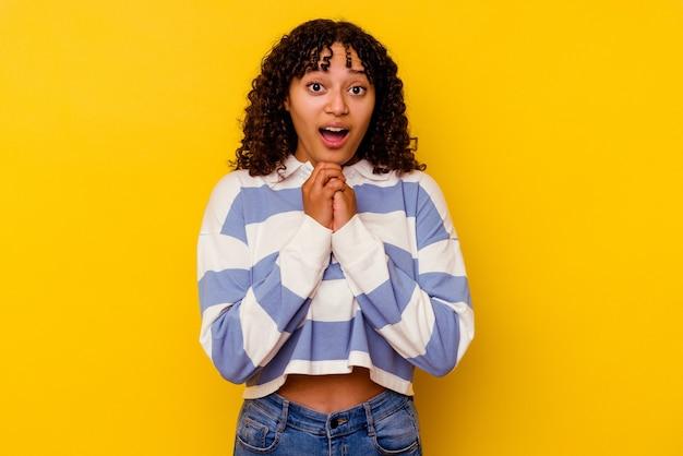 Jeune femme métisse isolée sur jaune priant pour la chance, étonnée et ouvrant la bouche regardant vers l'avant.