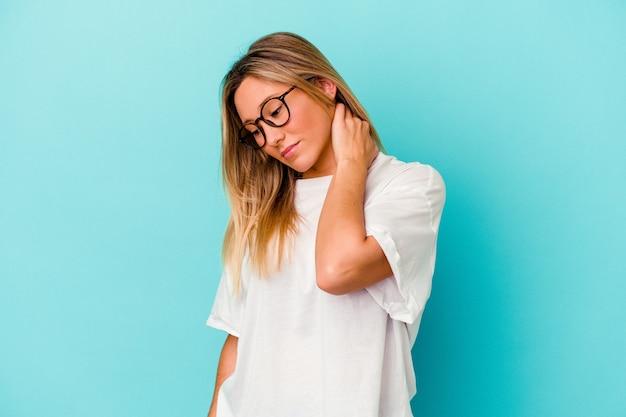 Jeune femme métisse isolée sur un mur bleu ayant une douleur au cou due au stress, en massant et en la touchant avec la main.