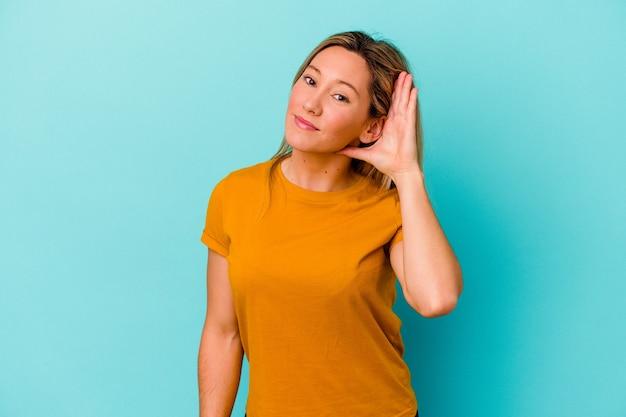 Jeune femme métisse isolée sur mur bleu essayant d'écouter un potin.