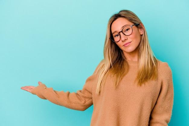 Jeune femme métisse isolée sur mur bleu montrant quelque chose sur l'espace de copie