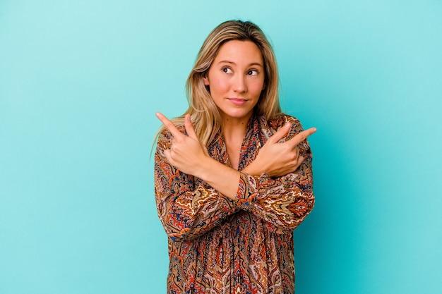 Jeune femme métisse isolée sur le mur bleu pointe sur le côté, essaie de choisir entre deux options.
