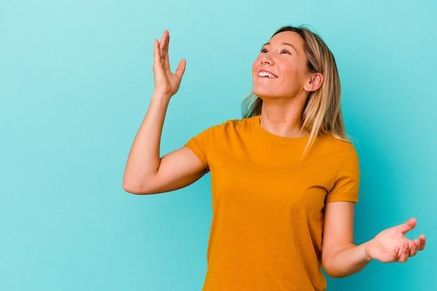 Jeune femme métisse isolée sur le mur bleu en riant une émotion naturelle, insouciante et heureuse.