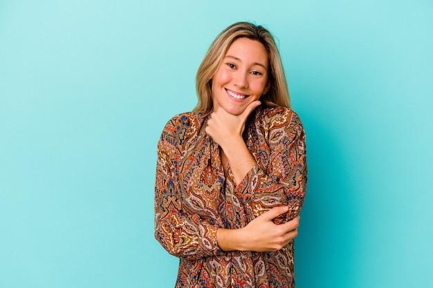 Jeune femme métisse isolée sur mur bleu souriant heureux et confiant, touchant le menton avec la main.