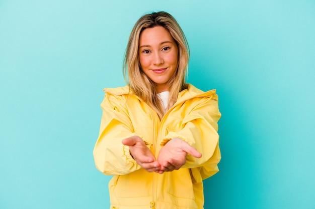 Jeune femme métisse isolée sur un mur bleu tenant quelque chose avec des palmiers, offrant à la caméra.