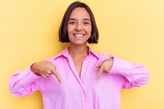 Jeune femme métisse isolée sur le mur jaune pointe vers le bas avec les doigts, sentiment positif.